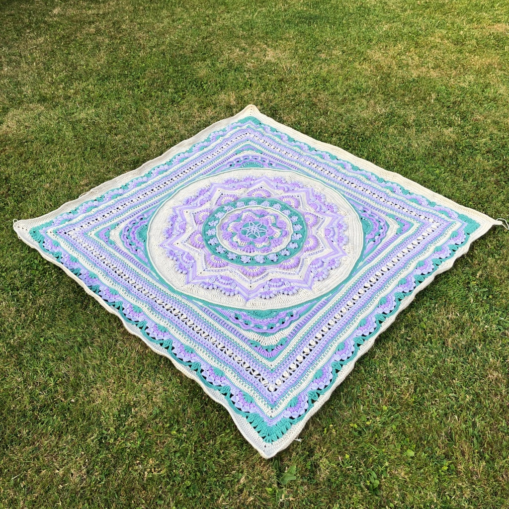 Image of a crochet blanket in colours of violet, Wisteria, green and parchment.