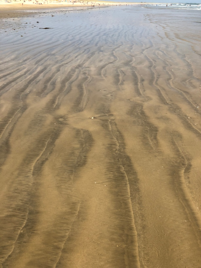 Patterns left in the sand by receding surf