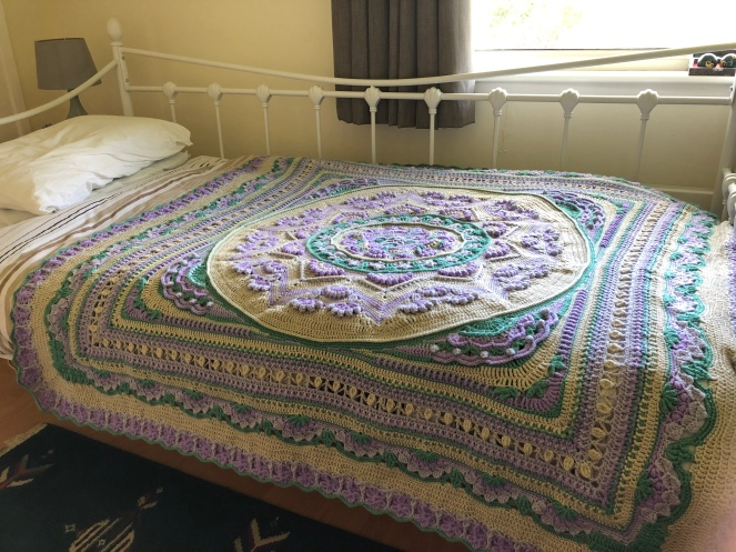 A crochet blanket laid over a single bed